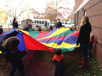 Early chilldhood students with children playing parachute games