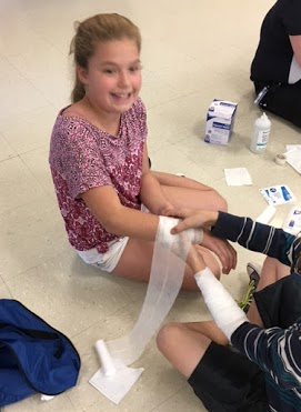 Student getting her arm wrapped during first aid training