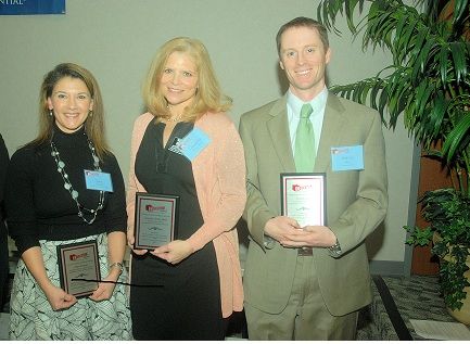 Three teachers holding awards