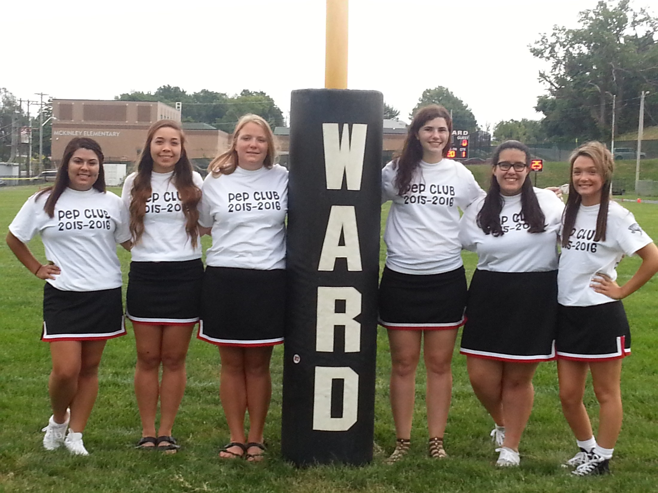 "Six girls gathered around a football goal post that says ""ward"" in shirts that say ""Pep Club 2015-2016"""