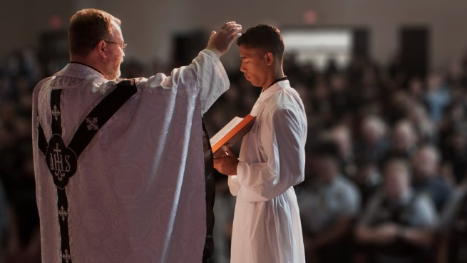 Priest raising hands while a boy holds a book for him.