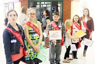 Kids standing in a group with awards and sashes
