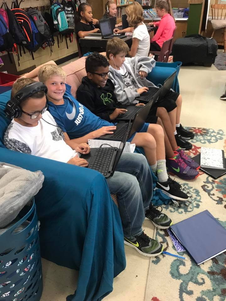 Students on a couch working on laptops