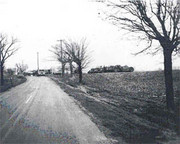 Black and white photo of empty feild next to a road