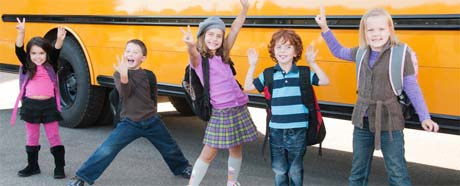 Kids celebrating in front of a school bus