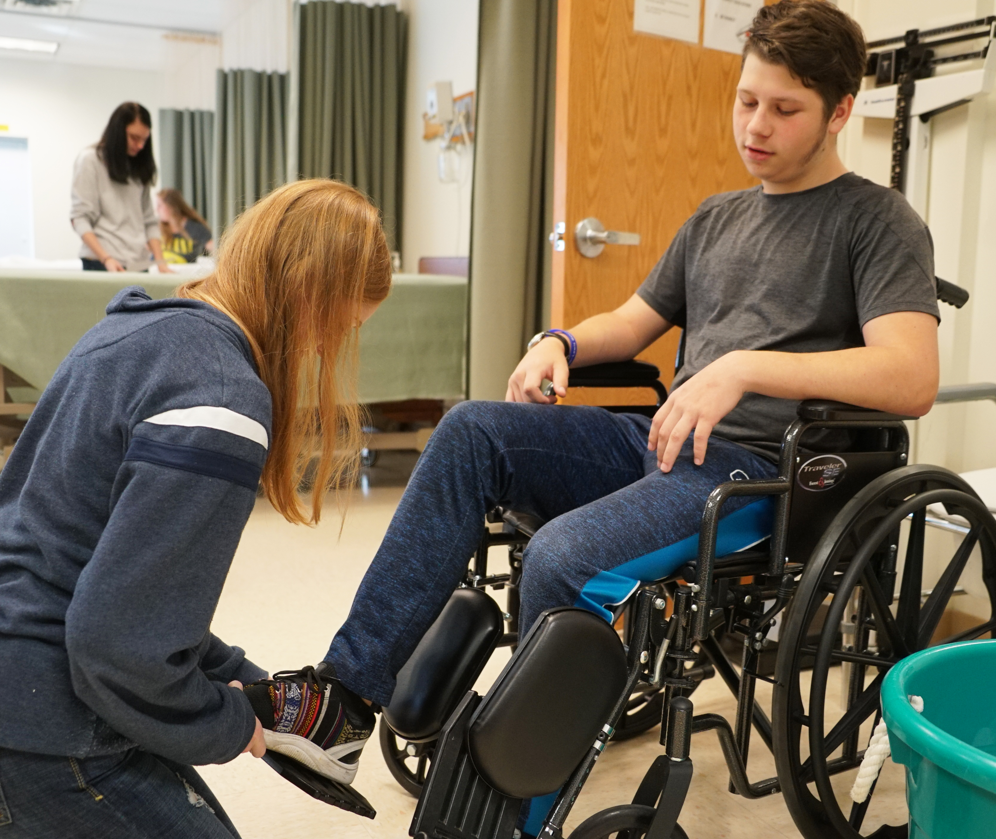 student assisting another student in wheel chair