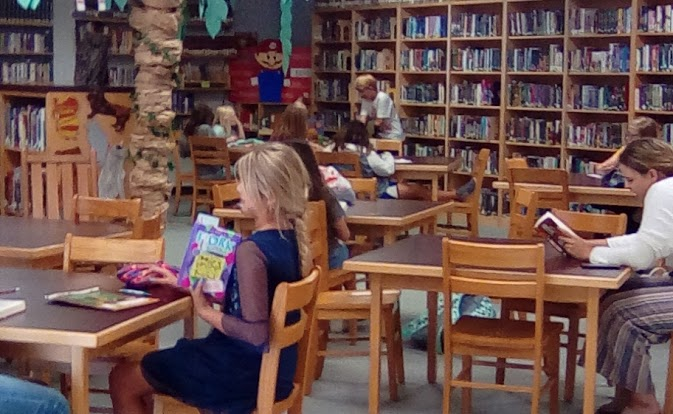 Students reading at tables, library shelves in the background