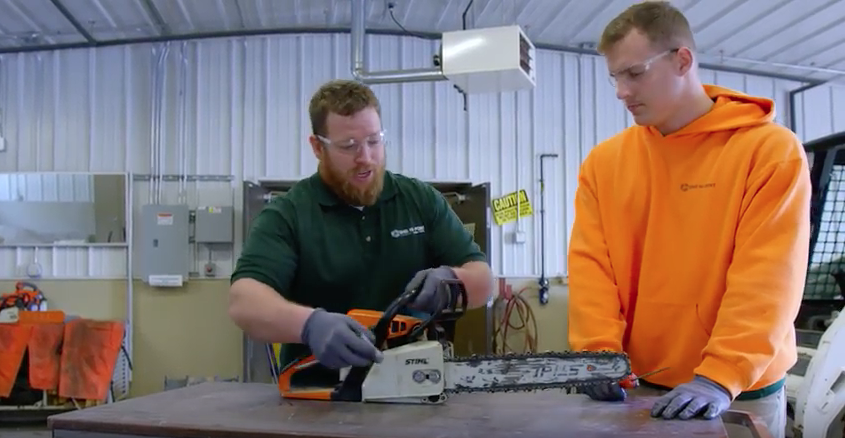Teacher and student looking at a chainsaw