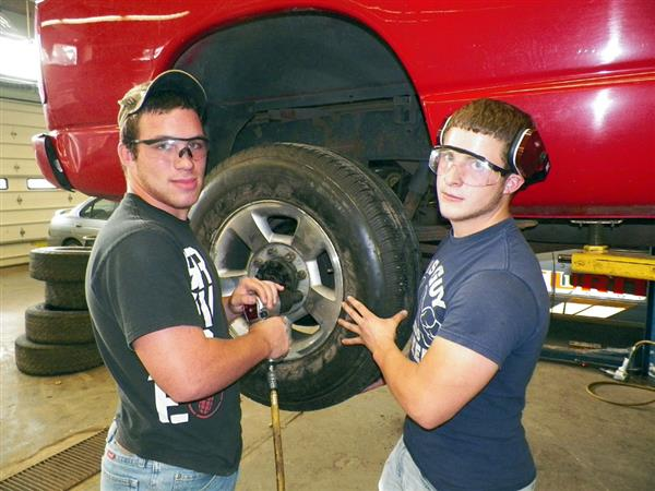 Two students working on a car tire