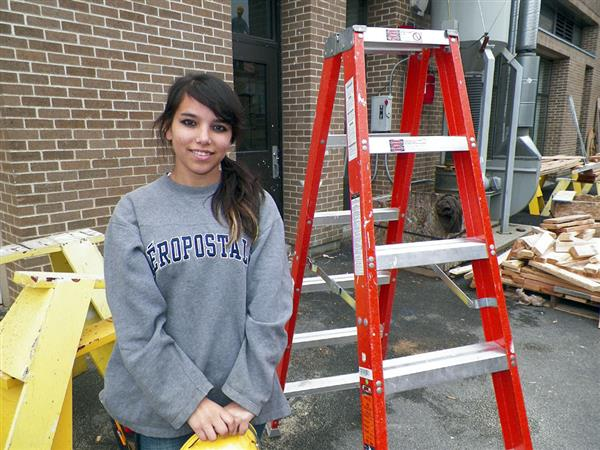 Student holding construction hat next to ladder