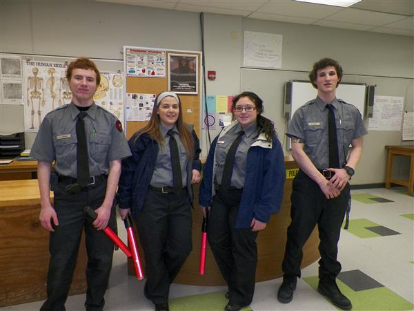 Four criminal justice students standing together in uniform