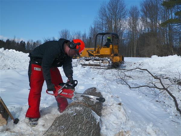 Student cutting a log with a chainsaw as other student plows snow in the background