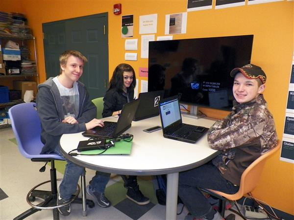 Three VP-TECH students sitting at a table with their laptops