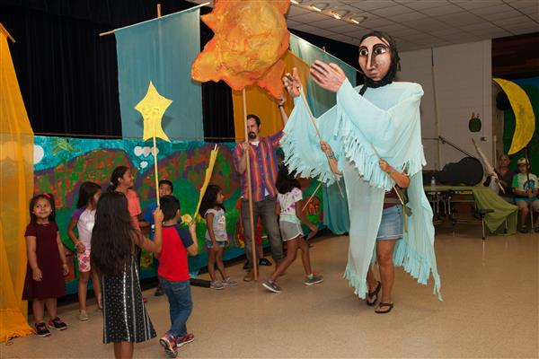 Migrant education students interacting with a large puppet