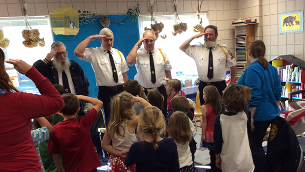 Volunteering officers saluting group of students