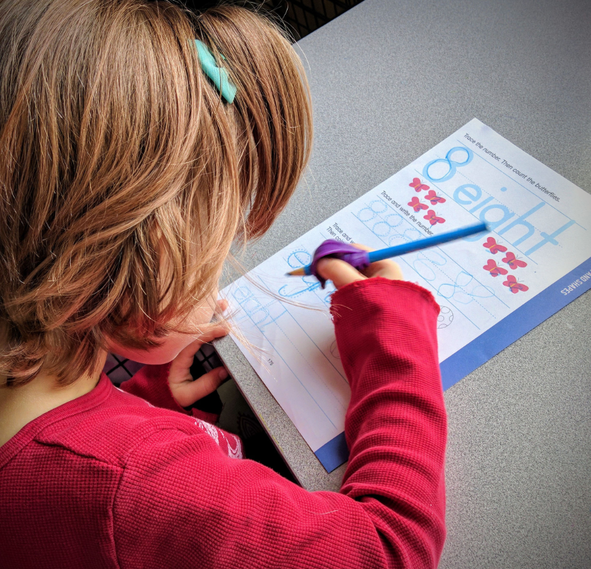 A student tracing her numbers and letters