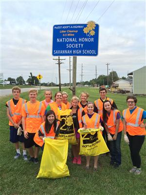 NHS students standing in front of highway sign with neon orange vests and trash bags