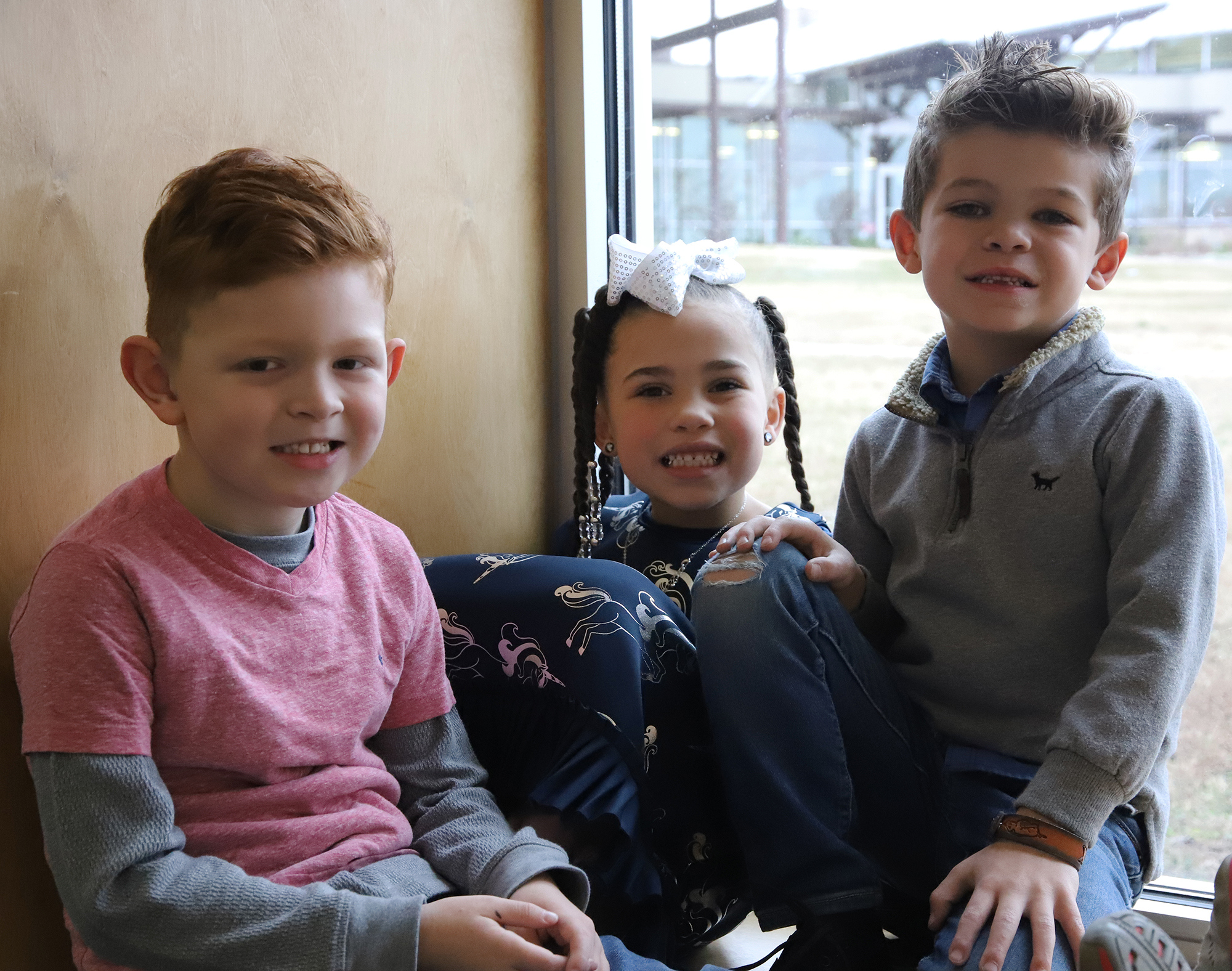Three current kindergarten students smile while posing in a window.