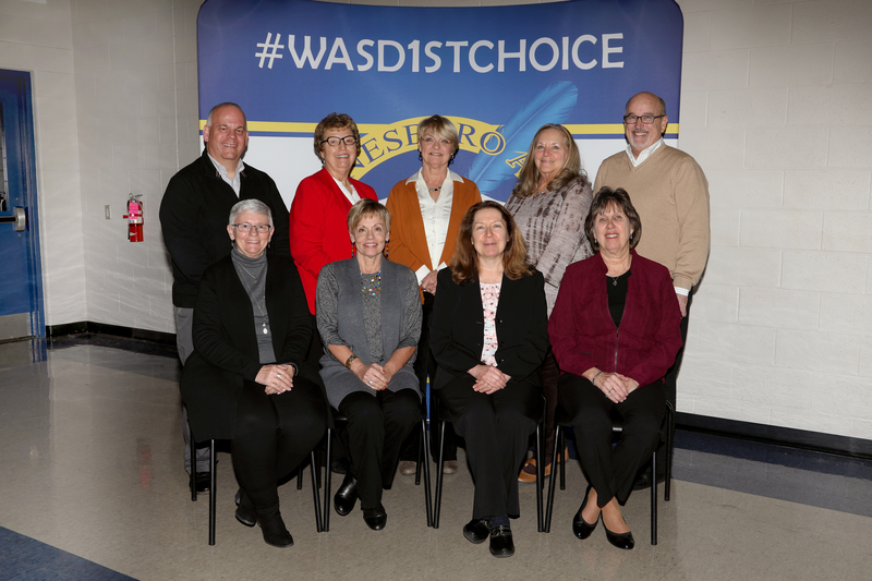 WASD Board of Directors sitting in front of a school banner