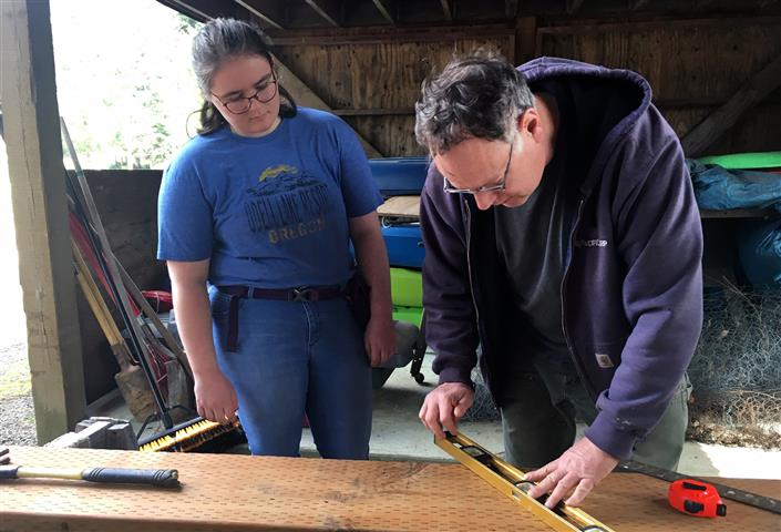 Mara Reese, a senior at Woodland High School, and her dad, Eric Reese, measure and cut lumber to build a deck and stairs for the family home