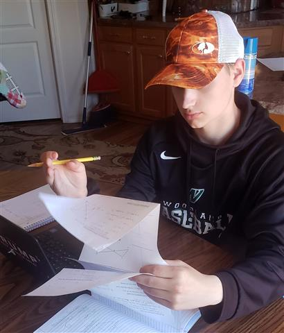 Colton Hall, a tenth grader at Woodland High School, works on a math test at home