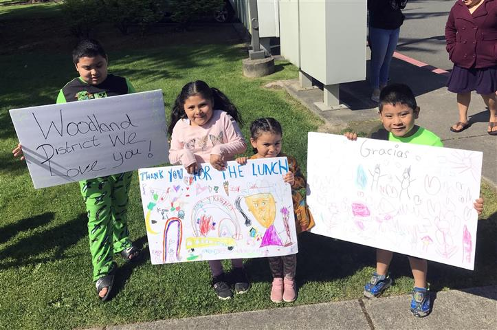 Students and their siblings made signs thanking Woodland Public Schools staff